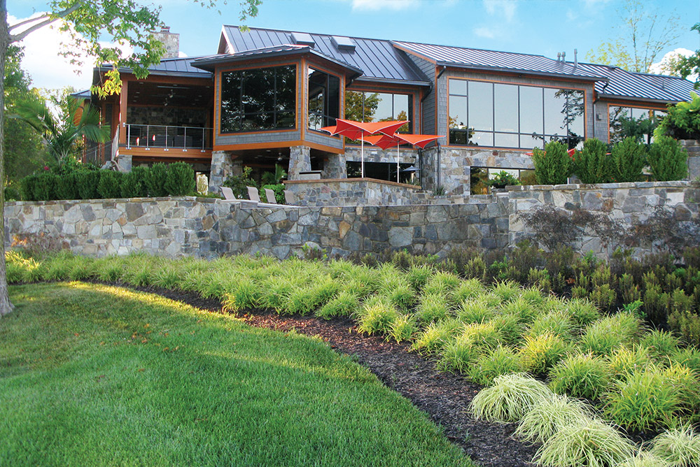Modern home, pool, stone wall and landscaping by OEG